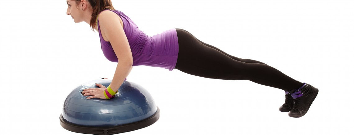 Studio shot of young athletic woman doing pushups on a bosu ball, isolated over white background
